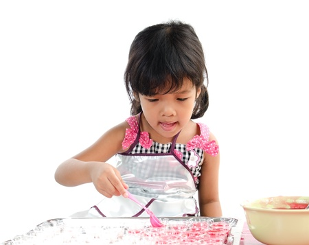 Little girl cooking on white background  photo