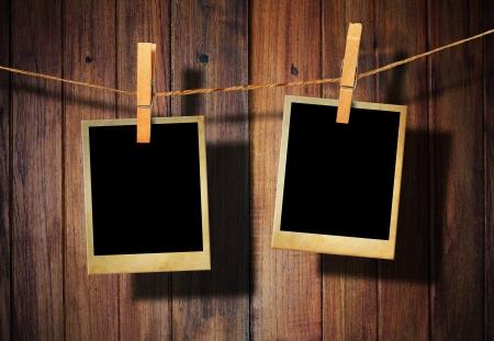 Old picture frame hanging on clothesline on wood background. Standard-Bild