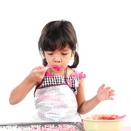 Little girl made jelly on white background. photo