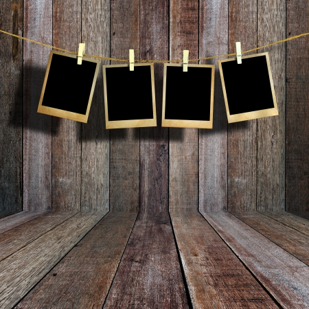 Old picture frame hanging on clothesline in vintage wood room  photo