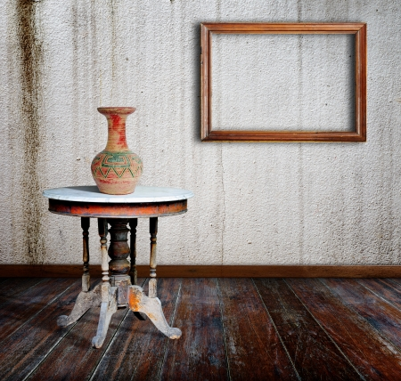 Vases, table and old Picture frame in grunge room. photo