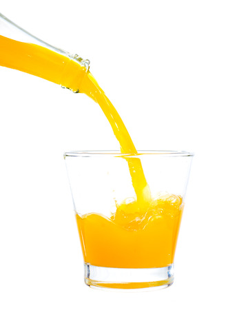 Pouring orange juice on a glass on white background photo