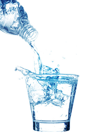 Pouring water on a glass on white