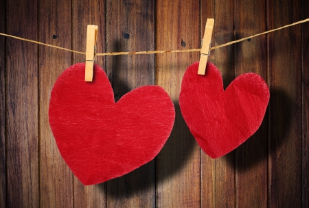 Red heart  hanging on clothesline on wood background  photo