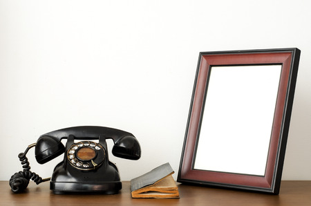 Old telephone and empty picture frame  photo