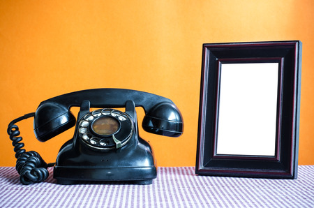 old office: Old telephone and empty picture frame. Stock Photo