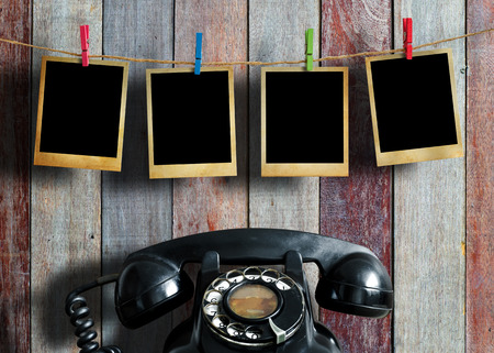 antique phone: Old picture frame hanging on clothesline and old telephone on wood background. Stock Photo