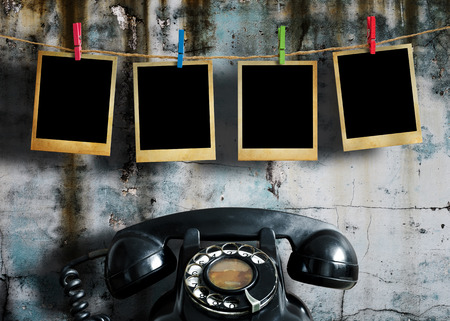 antique phone: Old picture frame hanging on clothesline and old telephone on grunge wall.