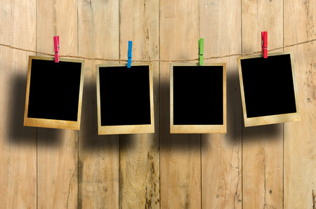 clothespin: Old picture frame hanging on clothesline on wood background. Stock Photo