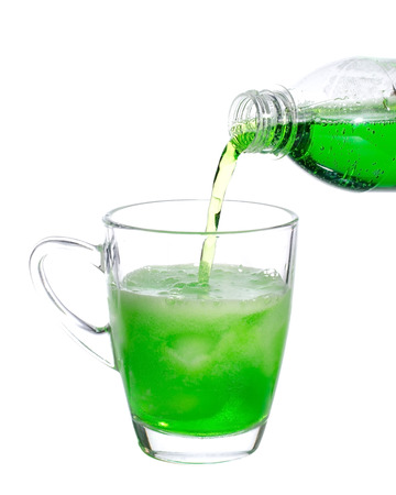 Pouring green soda on a glass on white background photo