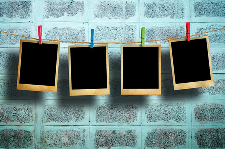 Old picture frame hanging on clothesline on grunge wall.