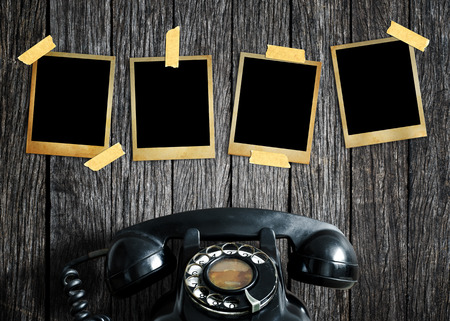 Old picture and old telephone on wood background. photo