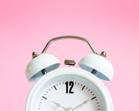 Alarm clock on pink background.