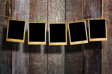 Old picture frame hanging on clothesline on wood background. photo