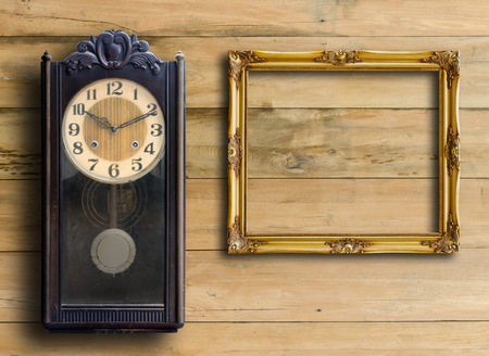 Old clock and empty picture frame on wood wall. photo