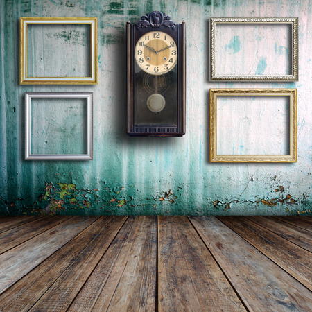 Old clock and empty picture frame in old room. photo