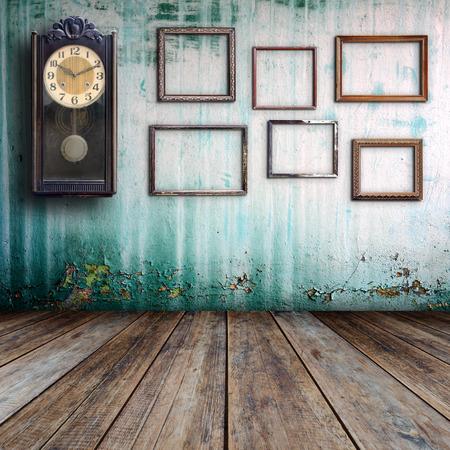 paredes de ladrillos: Antiguo reloj y el marco vacío en la vieja habitación.
