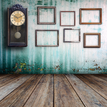 dirty room: Old clock and empty picture frame in old room. Stock Photo