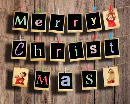 Merry christmas words hanging on clothesline on wood background. photo