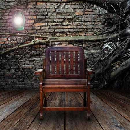 kerosene: Grunge room with kerosene lamps and armchair.