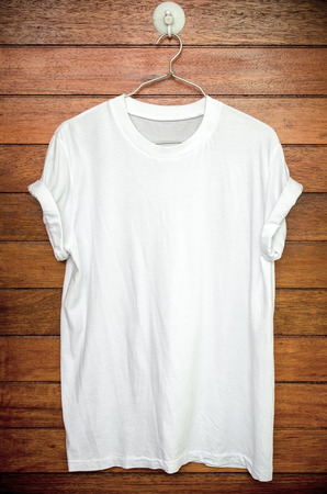 White t-shirt hang on wood wall. Stock Photo