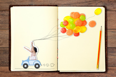 Girl driving a car and candy balloon. Design with paper craft put on book. photo