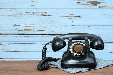 contact icons: Old telephone on wood background.