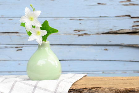 home accent: White flowers in the vase put on old wood. Stock Photo