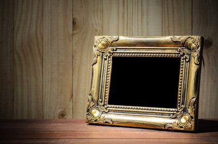 Old picture frame put on wood background. Standard-Bild