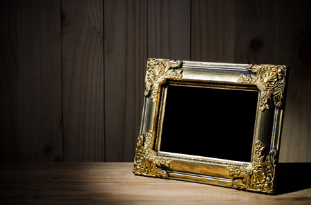 Old picture frame on wood background. photo
