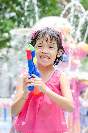 play popular: Little girl playing water in Songkran festival Thailand.