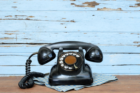 Old telephone on wood background.