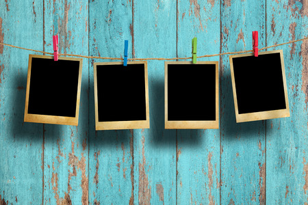 clothesline: Old picture frame hanging on clothesline on wood background. Stock Photo