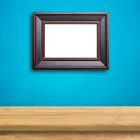 old picture: Old picture frame on blue wall.