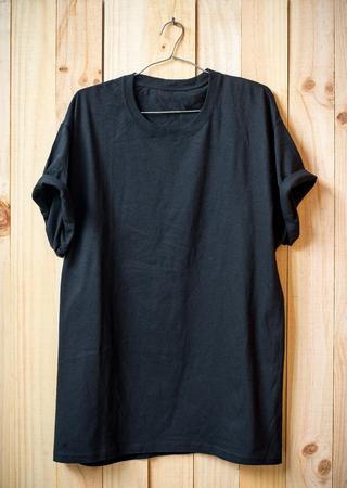 a shirt: Black t-shirt hang on wood wall.