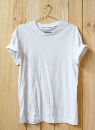 White t-shirt hang on wood wall. Standard-Bild