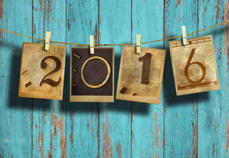 photo album: New year 2016 in old photo hanging on clothesline on wood background.
