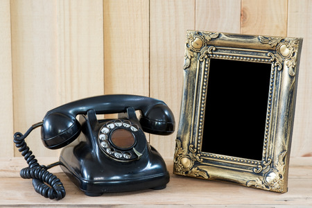 Old telephone and empty picture frame. Stock Photo