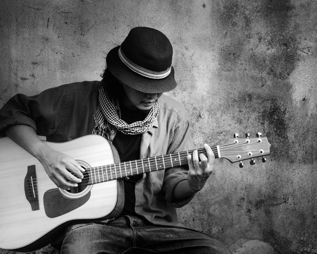 young musician: Man playing guitar. Black and white photo