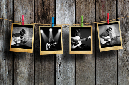 photo album: Guitarist photo hanging on clothesline on wood background.