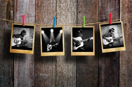 木材の背景に物干しに掛かっているギタリストの写真。