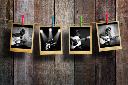 vintage photo: Guitarist photo hanging on clothesline on wood background.