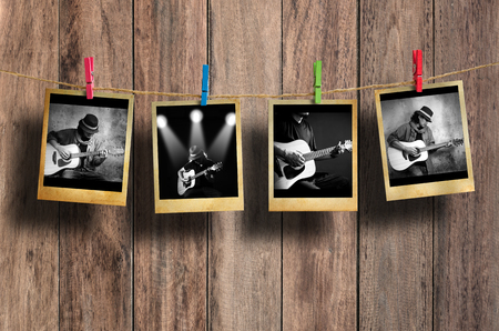 paper old: Guitarist photo hanging on clothesline on wood background.