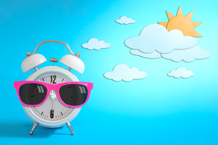 time of day: Alarm clock wearing sunglasses on day sky paper craft., Daytime concept.