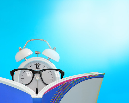 wearing spectacles: Alarm clock wearing spectacles reading a book., Reading time concept.