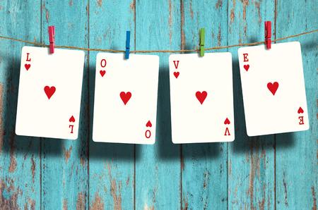 """Poker palabras """"ama"""" colgando de tendedero en el fondo de madera."""