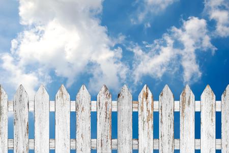 slats: Old wood fence on blue sky background.