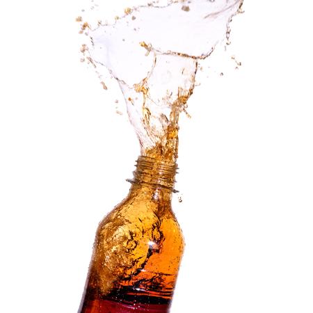 gaseosas: Soda salpique fuera de la botella en el fondo blanco. Foto de archivo