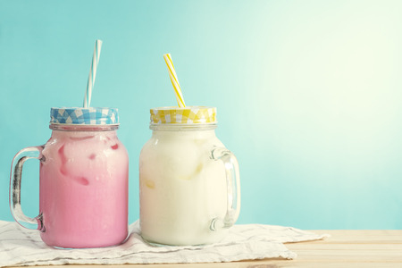 Milkshakes put on wooden in blue wall room. Pastel tone.