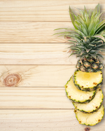 jhy: Pineapple with slices on wood background.
